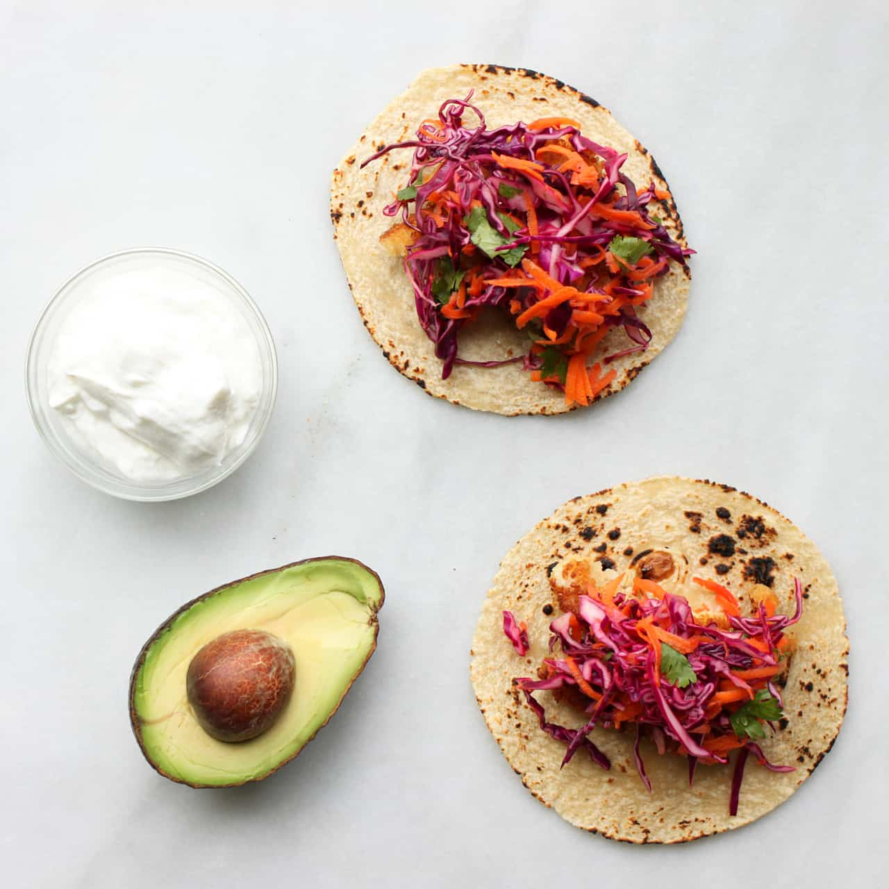 Easy fish tacos with red cabbage carrot slaw according for Cabbage slaw for fish tacos