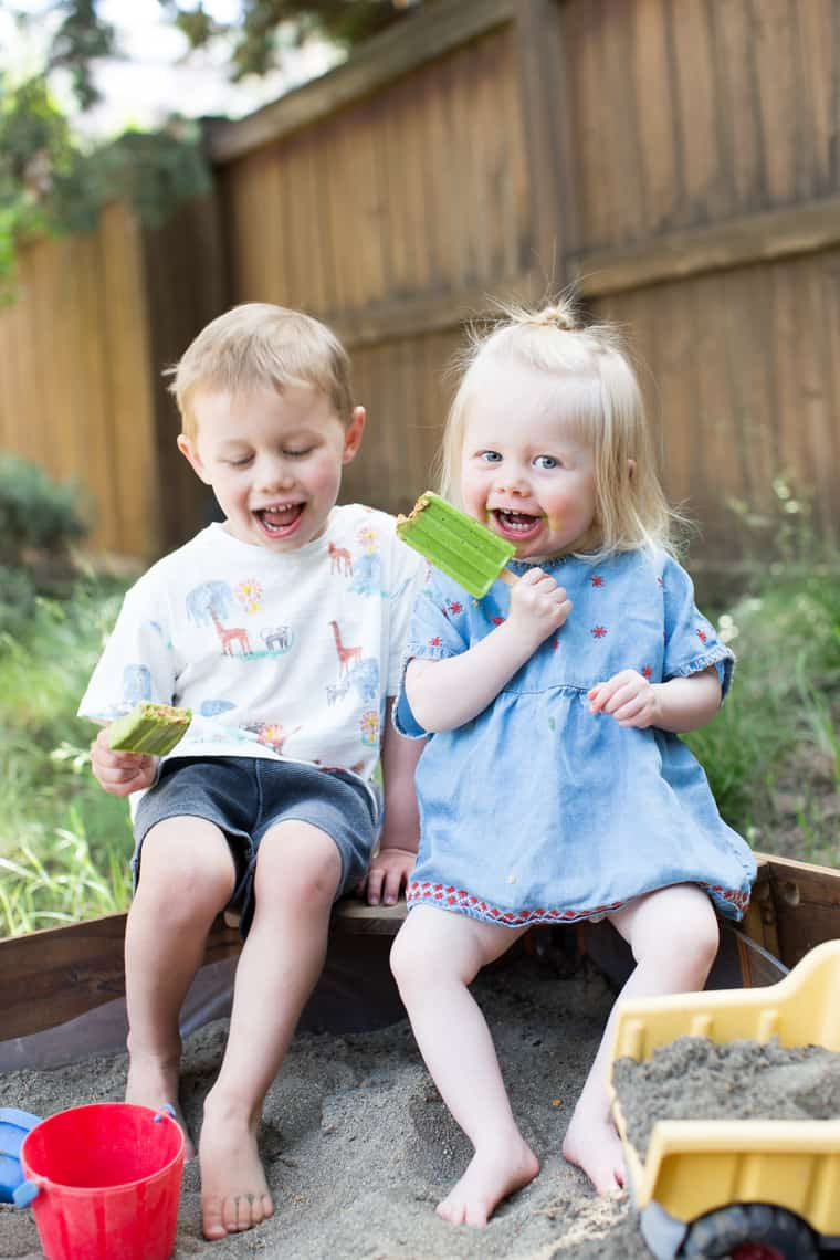 boy and girl toddlers eating healthy green smoothie popsicles