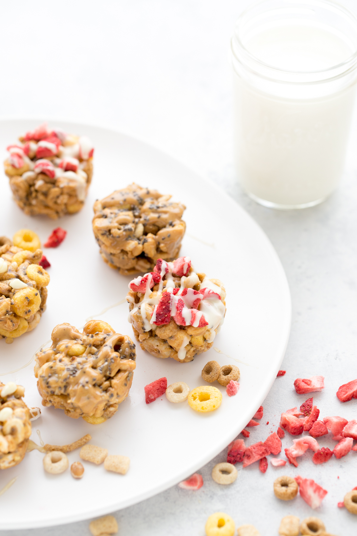 close up of no-bake peanut butter cereal cups on a plate with a mason jar of milk in the background